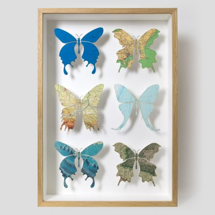 Six butterfly artwork created with a collection of beautiful maps in oak cabinet